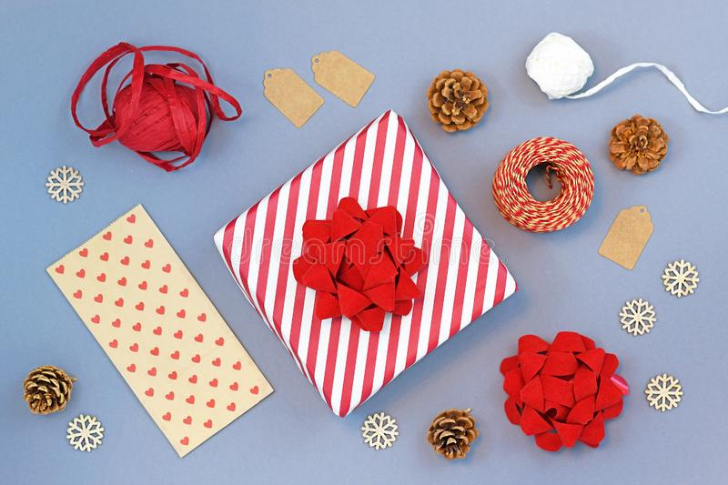 Seasonal christmas flat lay with red and white triped gift box with big ribbon, gift wrapping material, pine cones royalty free stock image
