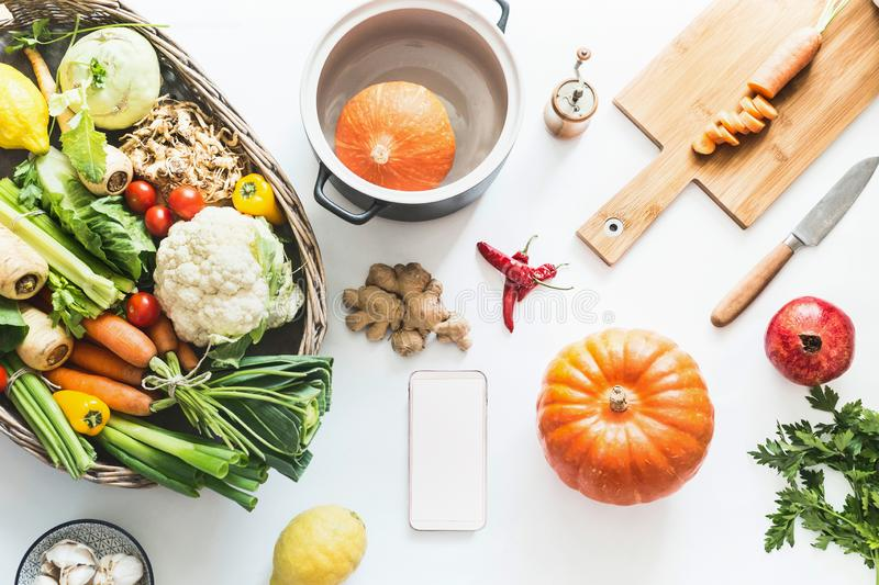 Seasonal cooking flat lay.  Smartphone with blank white screen and fresh organic vegetables ingredients , pumpkin , cooking pot , royalty free stock image