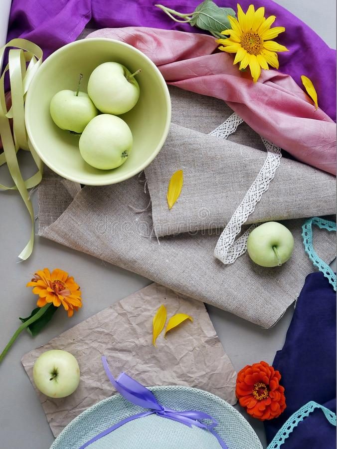 Seasonal decorative composition, still life. Summer, autumn. Apples, yellow petals, green hat and fresh flowers on a light background of gray canvas and pink and stock photo