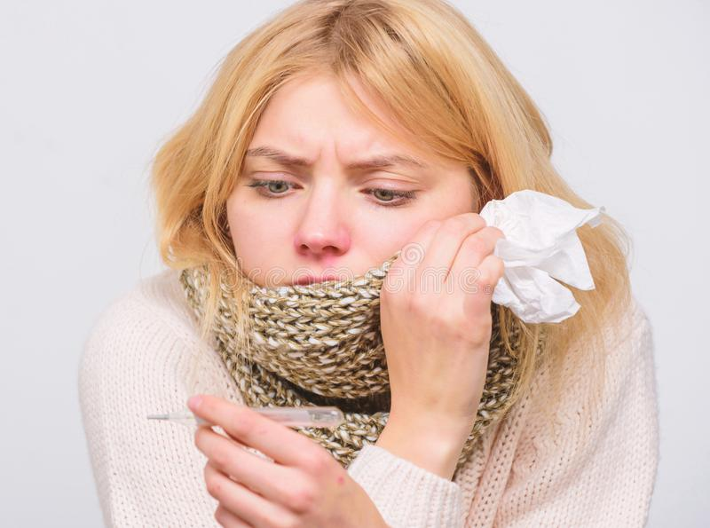 Seasonal flu concept. Woman feels badly. How to bring fever down. Fever symptoms and causes. Sick girl with fever. Girl. Sick hold thermometer and tissue stock image
