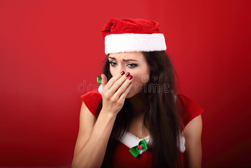 Seasonal flu. Unhappy frustration sick woman coughing in the han. D in christmas clothing on red background stock photography