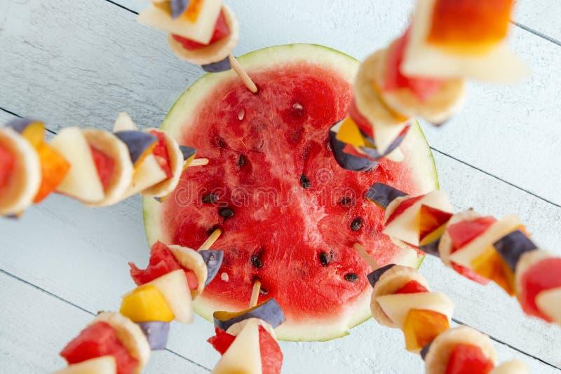 Seasonal fruit salad served on barbecue sticks royalty free stock image
