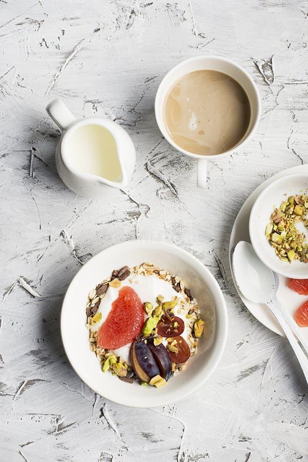 Seasonal healthy breakfast: yoghurt, chocolate granola, pink grapefruit, grapes, pistachios. Top view. Copy space. flat stock image