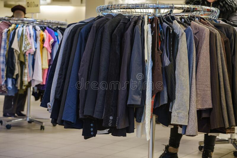 Seasonal sale at a clothing store. Hangers with clothes in clothes outlet stock photos