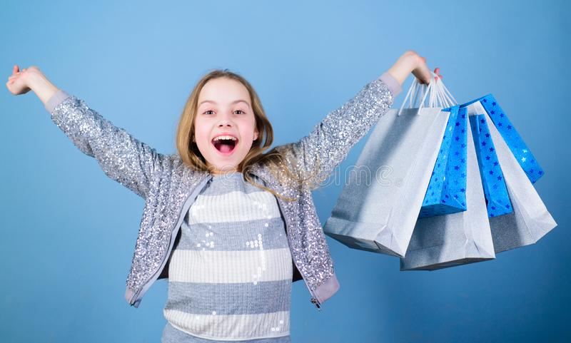 Seasonal sale. Fashion girl customer. Happy child in shop with bags. Shopping day happiness. Birthday girl shopping. Fashion boutique. Fashion trend. Fashion royalty free stock photography