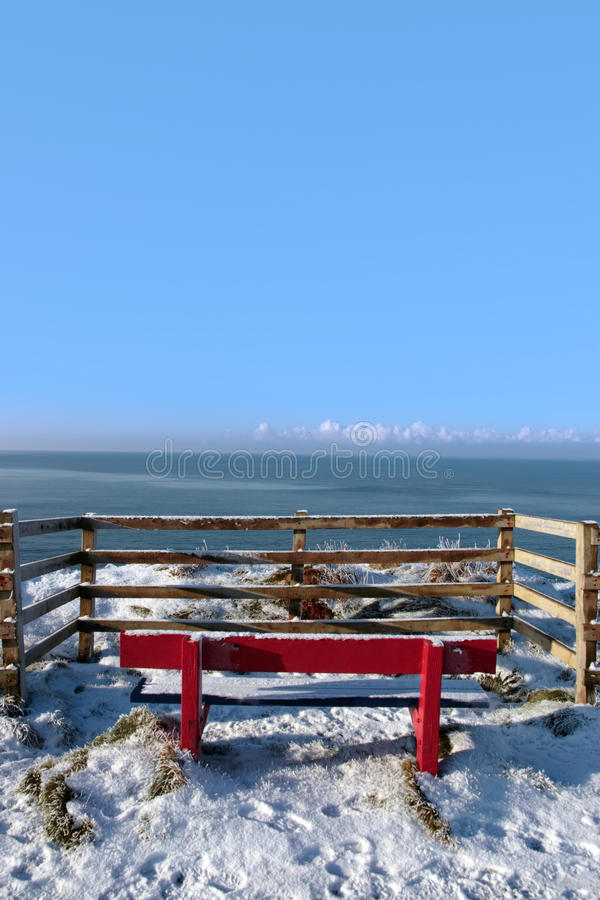Seasonal snowy frost covered red bench sea view royalty free stock photos