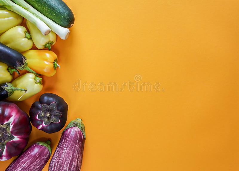 Seasonal vegetables of orange, green, yellow and purple colors lie freely on a yellow background royalty free stock image