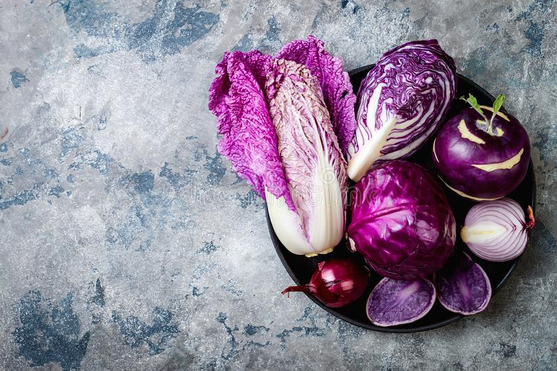 Seasonal winter autumn purple vegetables over gray stone table. Plant based vegan or vegetarian cooking concept. Clean eating food. Seasonal winter autumn purple royalty free stock photo