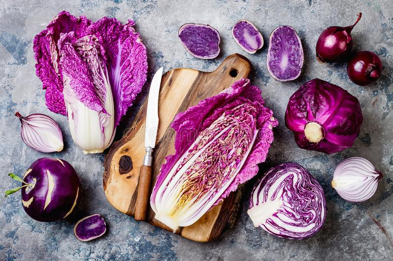 Seasonal winter autumn purple vegetables over gray stone table. Plant based vegan or vegetarian cooking concept. Clean eating food. Seasonal winter autumn purple stock photography