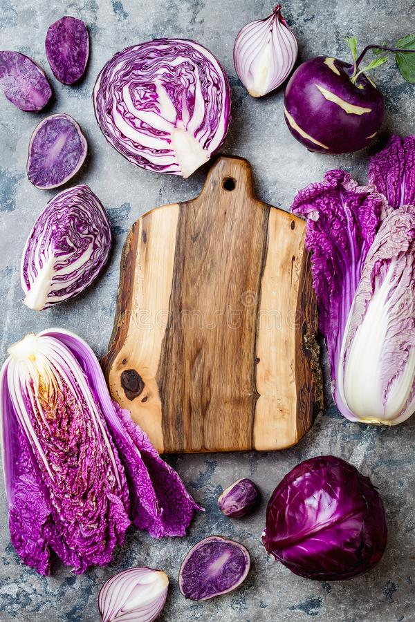 Seasonal winter autumn purple vegetables over gray stone table. Plant based vegan or vegetarian cooking concept. Clean eating food. Alkaline diet stock photos