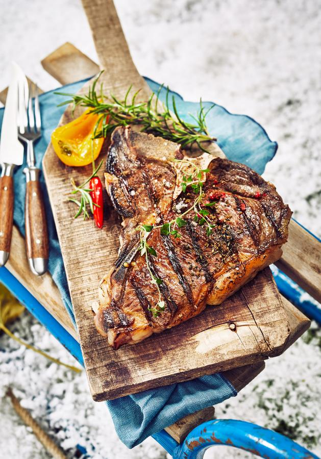 Seasoned grilled T-bone steak at a winter BBQ stock photography