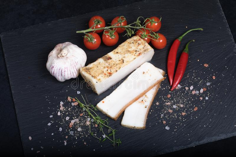 Seasoned lard on black stone plate. Close up of seasoned lard on black stone plate with garlic, chilli and cherry tomatoes stock photos
