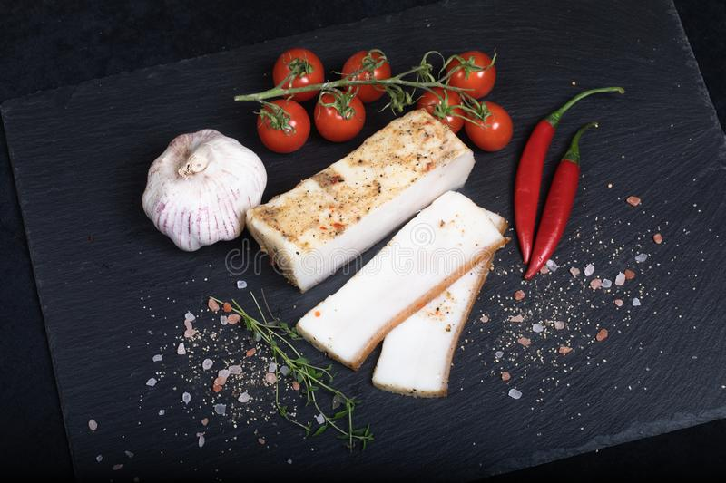 Seasoned lard on black stone plate. Close up of seasoned lard on black stone plate with garlic, chilli and cherry tomatoes royalty free stock images
