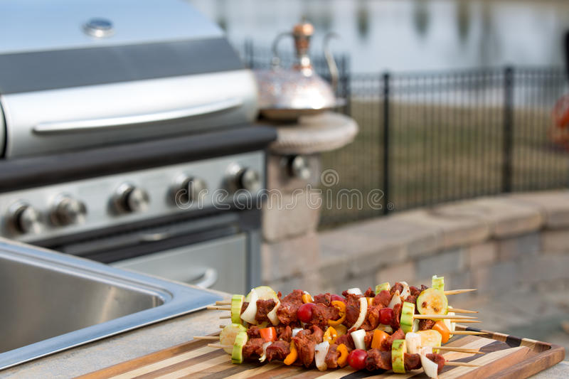 Skewrs and Barbecue. Seasoned meat skewers with vegetables on multicolored cutting board, on outside kitchen counter top next to the barbecue stock image