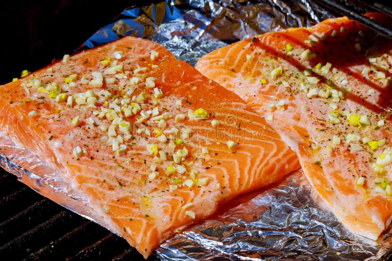 seasoned salmon fillet cooking over grill stock photo