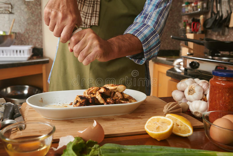 Seasoning dish. Close-up image of cook adding pepper to cooked dish stock photography