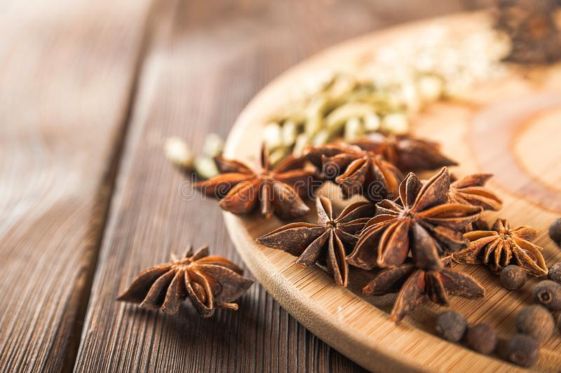 Seasoning on a textured wooden background close-up and copy space. Cinnamon, star anise, fennel, cloves, seasoning tea masala as a royalty free stock images
