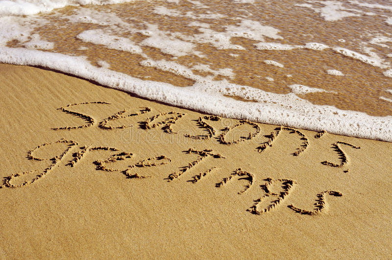 Seasons greetings on the beach, with a retro effect. Text seasons greetings carved on the sand of a beach, with a retro effect stock image