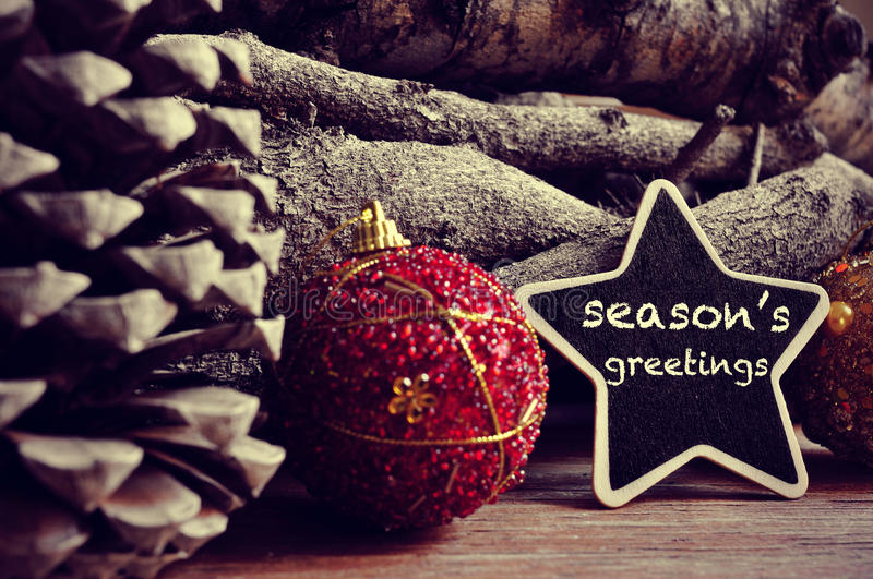 Seasons greetings. The text seasons greetings written in a star-shaped blackboard and some christmas balls, pinecones and a pile of logs in the background stock photo