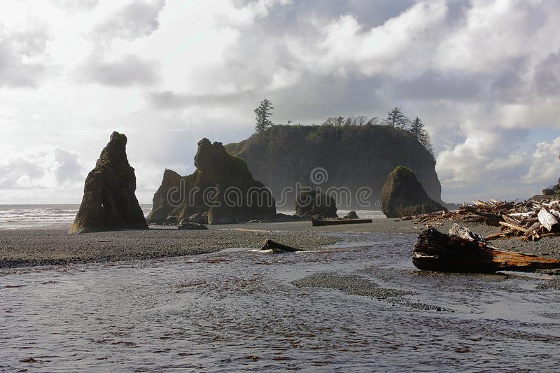 Seastacks and Dark Clouds at Ruby`s Beach, Olympic National Park, Washington. A creek is running past the seastacks and driftwood on the gravelly Pacific beach royalty free stock images