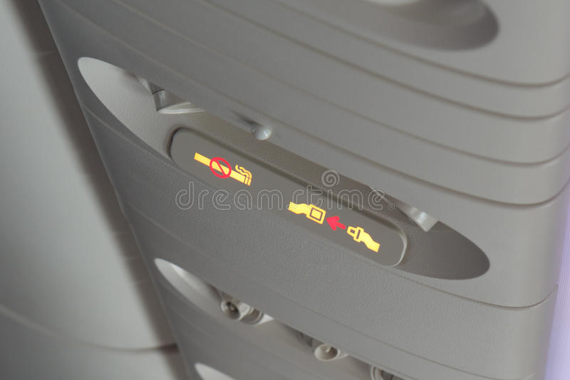 Seat belt and no smoking signs in aircraft royalty free stock photo