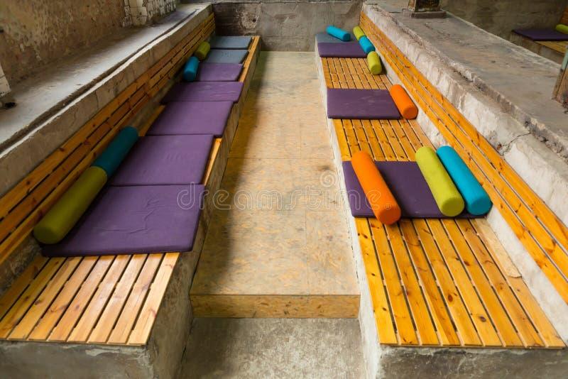 Seat dat van houten blokken en met multi-colored hoofdkussens van dif wordt gemaakt royalty-vrije stock afbeeldingen