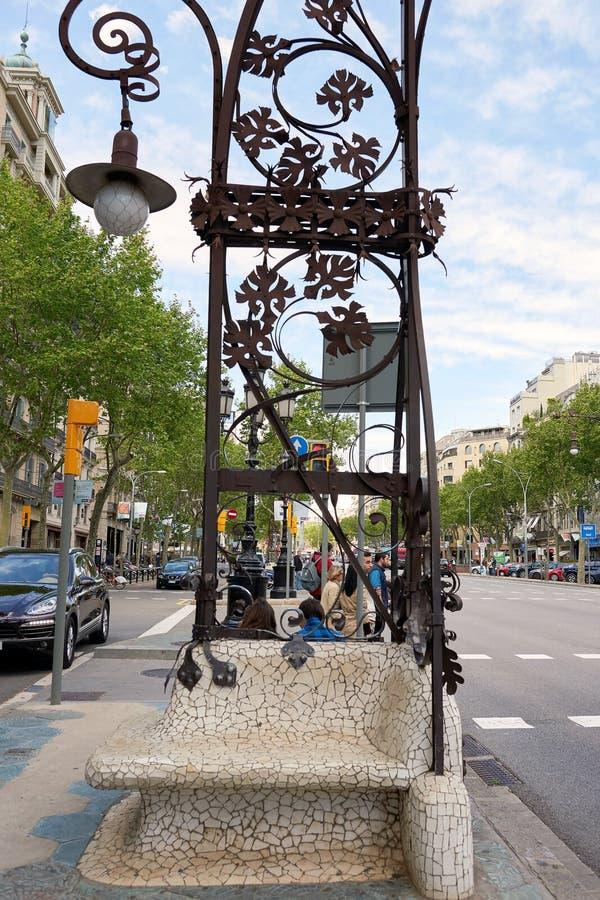 Seat a fait dans la mosaïque en pierre à partir d'un lampadaire au-dessus du fer situé sur la promenade appelée De Gracia, à côté photographie stock