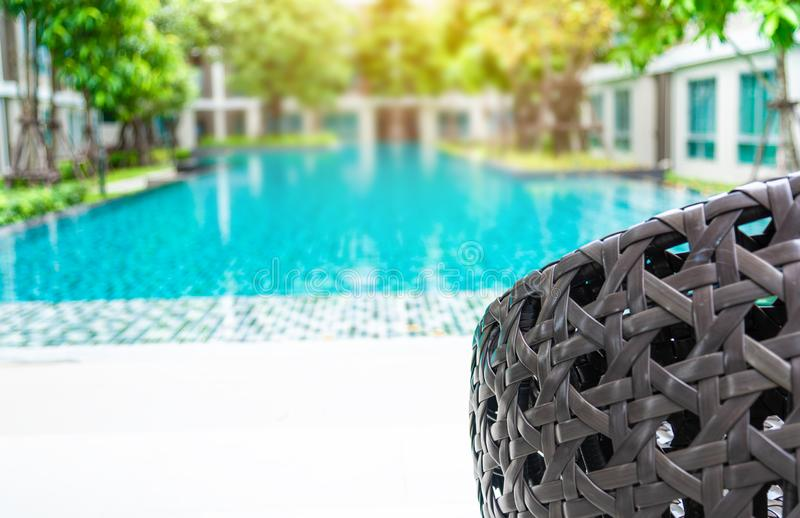 The seat lounger ,brown rattan chairs beside swimming pool with background is blurred of modern condominium or hotel or resort in royalty free stock photos
