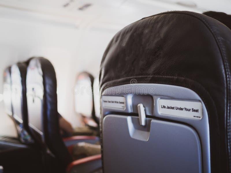 Seat-rijen in een vliegtuigcabine, Binnenlands van commercieel vliegtuig met onherkenbare passagiers op hun zetels tijdens vlucht stock fotografie