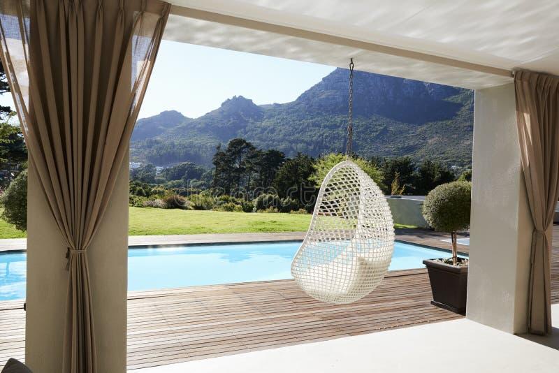 Seat suspendido al lado del Decking alrededor de la piscina al aire libre fotos de archivo libres de regalías