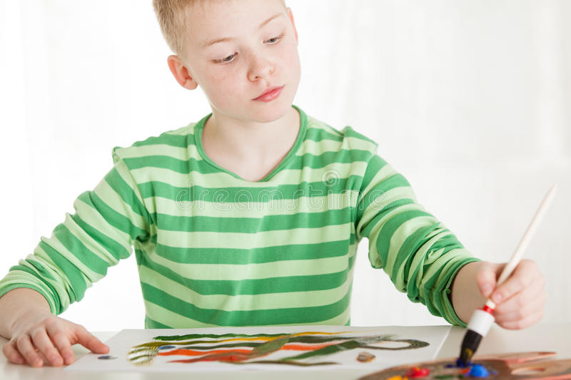 Seated boy paints with brush on white paper stock images