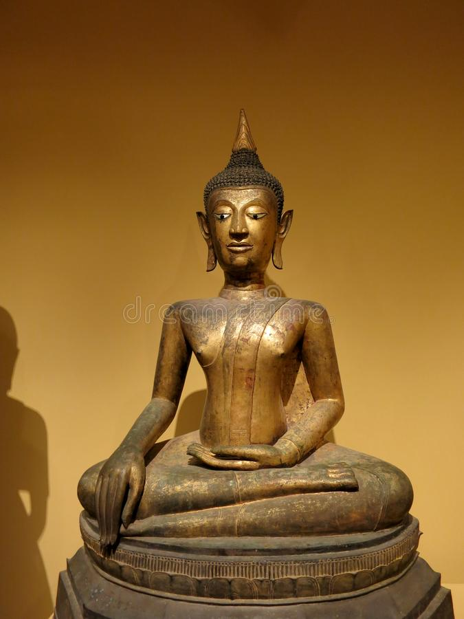 Seated Buddha. HonoluIu - May 9, 2015: Seated Buddha, 16th century, Artist is Anonymous, Medium Gilt bronze, inlaid shell and black lacquer, Geography: Thailand royalty free stock photo