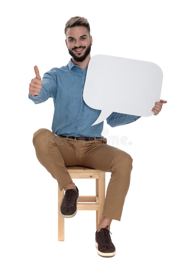 Seated business man showing ok gesture while holding talk sign stock image