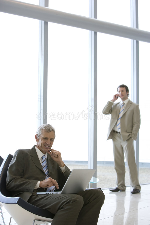 Seated businessman with laptop royalty free stock image