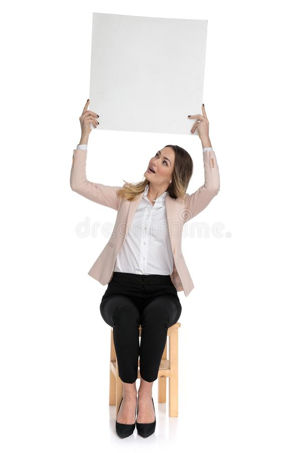 Seated businesswoman in pink suit holds board and looks up stock photos