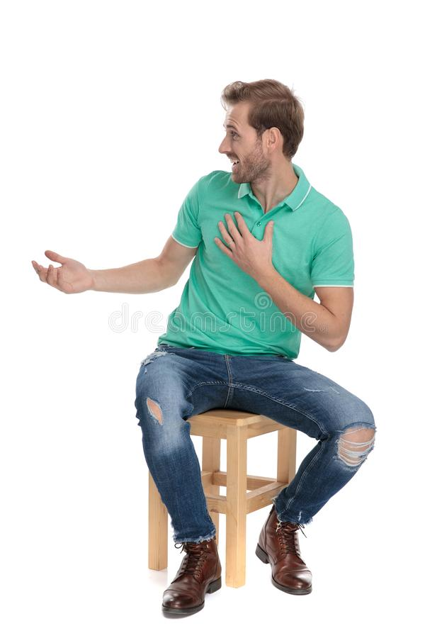 Seated casual guy in green polo shirt looking amazed. On white background royalty free stock photos