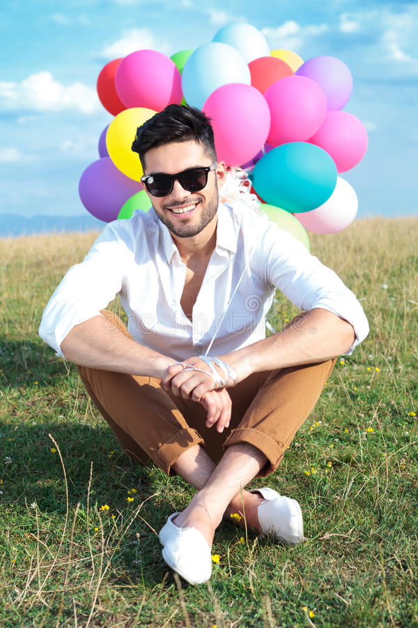 Seated casual man with balloons and sunglasses stock photos