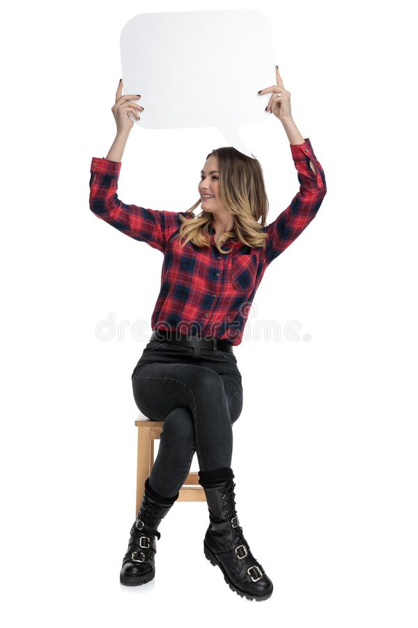 Seated casual woman presenting speech bubble overhead and looking sideways stock photo