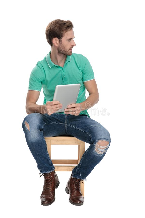 Seated fashion guy looking away with pad in hands. Seated fashion guy in green polo shirt looking away with pad in hands on white background stock photos