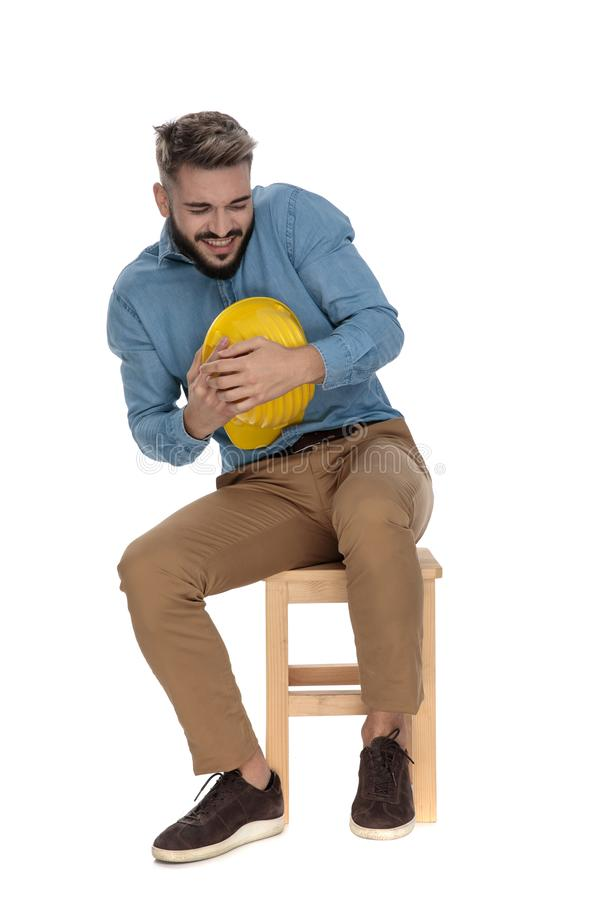 Seated feared man defending his yellow safety hat. Seated feared man in blue jeans shirt defending his yellow safety hat on white background stock photo