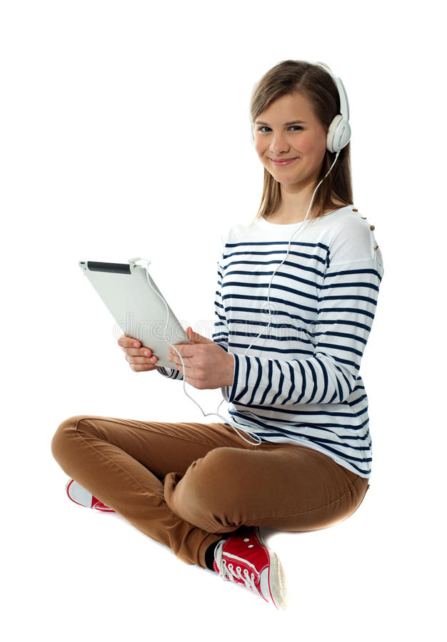 Seated Girl Enjoying Music On Portable Device Stock Photos
