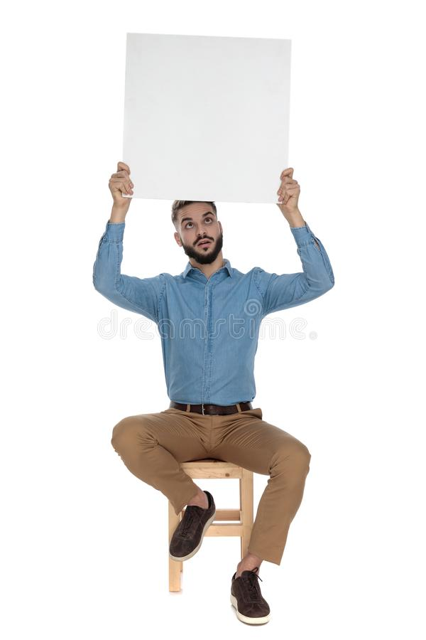 Seated goofy man holds blank billboard up in the air. Seated goofy man in blue jeans shirt holds a blank billboard up in the air on white background royalty free stock images