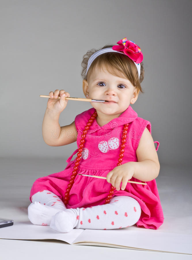 Seated little girl holding a paintbrush royalty free stock image