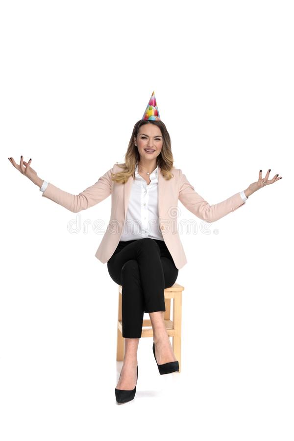 Seated smart casual woman wearing birthday hat makes greeting gesture. On white background royalty free stock photos