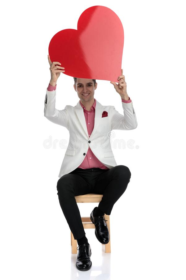 Seated smiling young businessman holds a red heart up royalty free stock images