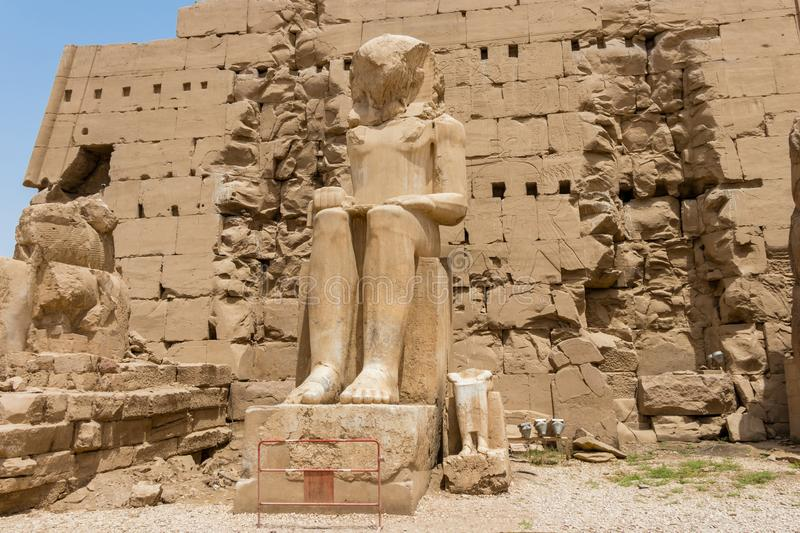 Seated statue in front of the seventh Pylon of the Amun Temple, Karnak, Luxor, Egypt. The Temple of Amun is the largest religious building in the world and royalty free stock image