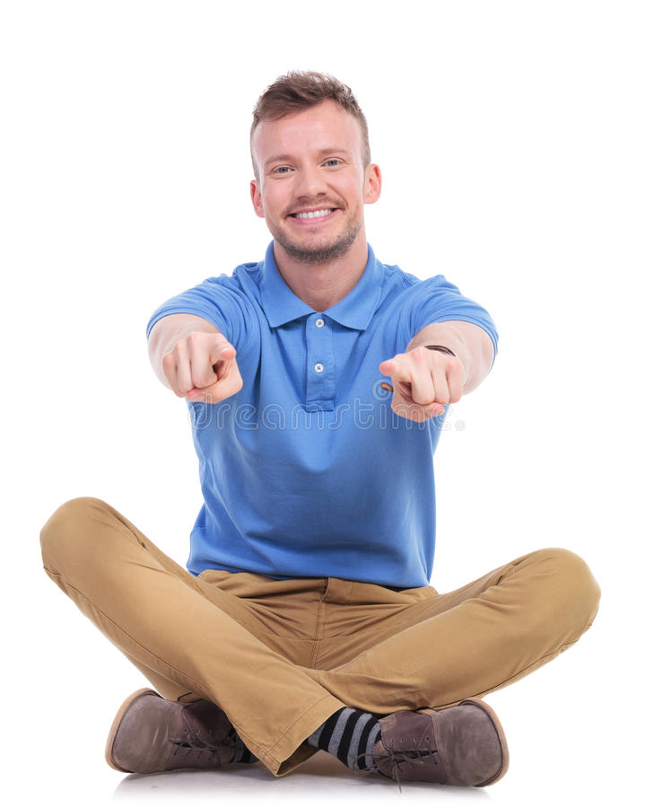 Seated young casual man points with both hands royalty free stock photo