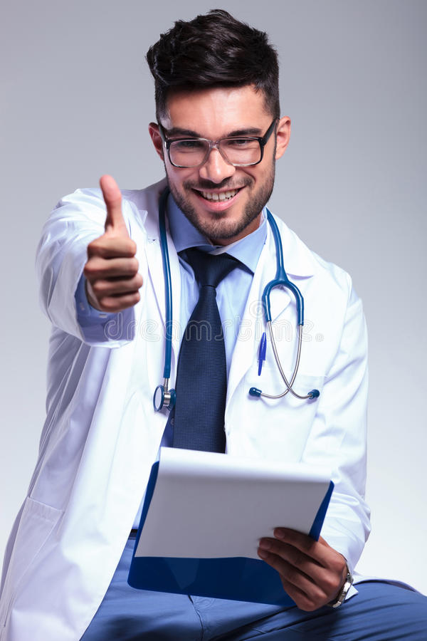 Seated young doctor shows ok to you. Young male doctor giving the thumb up to the camera, with a smile on his face. on gray background royalty free stock image