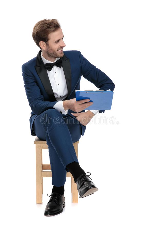 Seated young guy in blue suit giving his clipboard royalty free stock photos