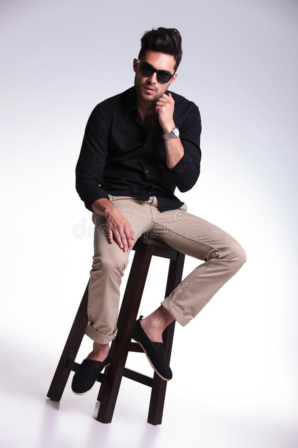 Download Seated Young Man Adjusting His Shirt Stock Photo - Image: 33657464